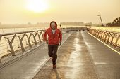 Positive Young Sprinter Running On A Bridge poster