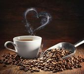 Coffee cup and coffee beans with bag, scoop and steam in heart shape on dark wooden background poster