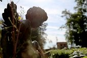 Beautiful Cupid Angel Statue With Wings On Back In Vintage Garden. Cupid Angel Statue Consisting Of  poster