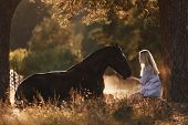 Portrait Of Beautiful Young Woman With Blond Hair Sitting In Front Of Lying Horse And Feed It From H poster
