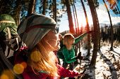 Two Travelers Close Up. Girlfriends Are In The Winter Forest. Two Women With Backpacks And Trekking  poster