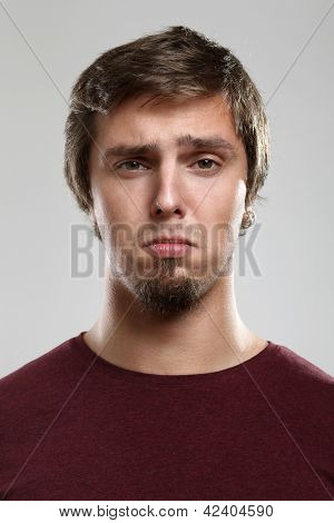 Portrait of young man with sad expression  isolated over background