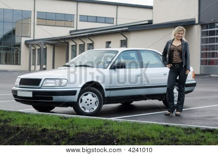 Blonde Girl With A Car At Empty Parking Place.