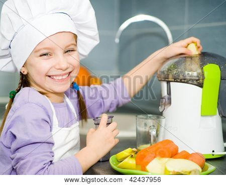 smiley little girl making fresh apple juice with a juice extractor