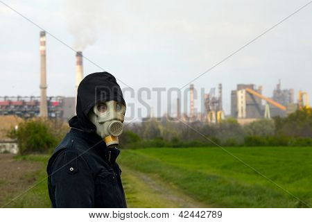 Man in gas mask near a high pollution metal factory