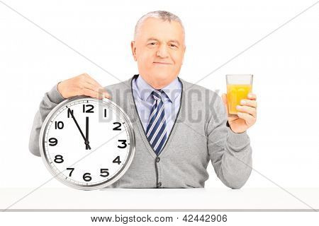 Smiling gentleman sitting and holding a wall clock and glass of orange juice isolated on white background