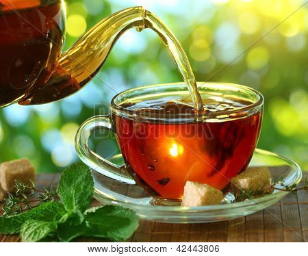 Pouring tea from a teapot into a cup on a blurred background of nature.