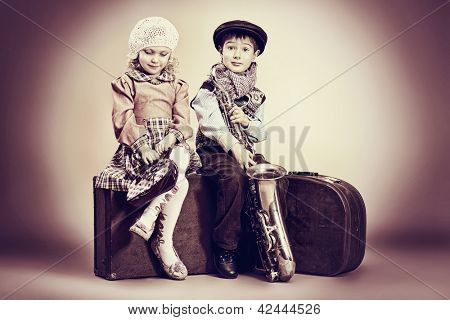 Cute little boy with his old saxophone is sitting on a suitcase with charming little lady. Retro style.