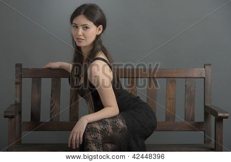 Beautiful Woman In Elegant Dress Posing In Studio Sitting On Bench