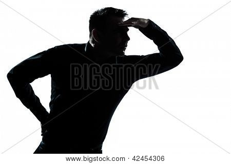 one caucasian man portrait looking away forward gesture shielding eyes silhouette in studio isolated white background