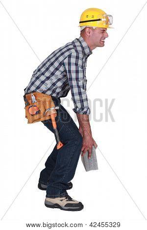 Mason struggling to carry brick