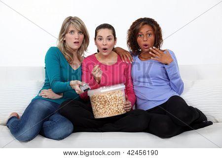 Three women eating popcorn whilst watching film