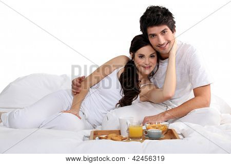a couple having breakfast on bed