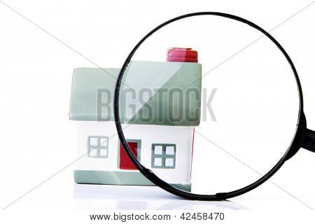 Magnifying glass inspecting a model single home building structure. Isolated on white. Real estate search concept.