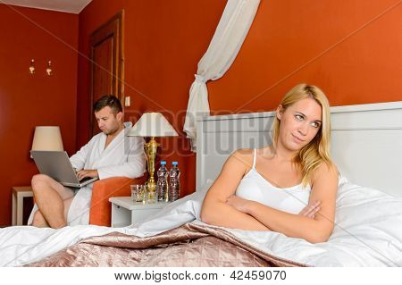 Resentful girl sitting bed room after fight boyfriend