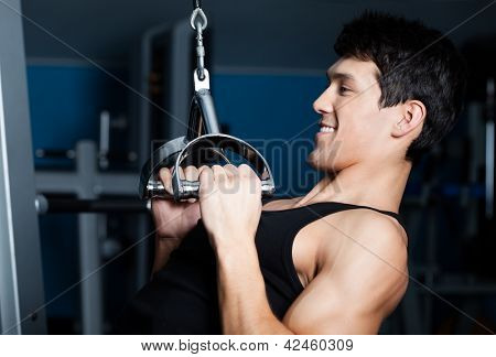 Athletic young man works out on simulator in gym
