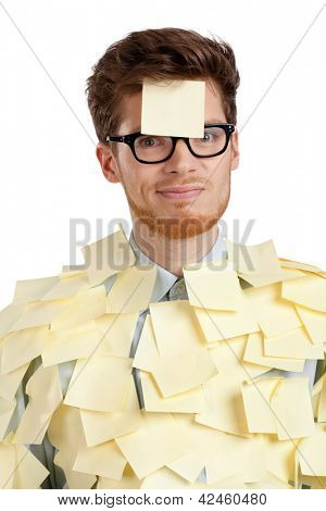 Unhappy young man with a sticky note on his face, covered with yellow stickers, isolated