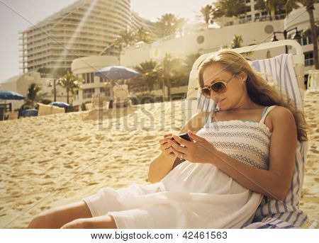 Woman Using her smartphone at the beach