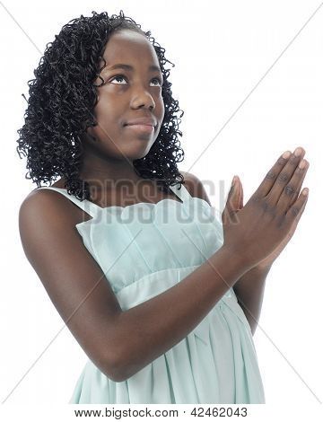 Close-up of a beautiful preteen looking heavenward as she holds her hands in prayer.  On a white background.