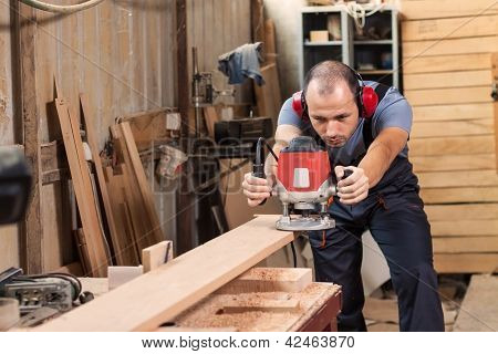 Carpenter With An Electric Router