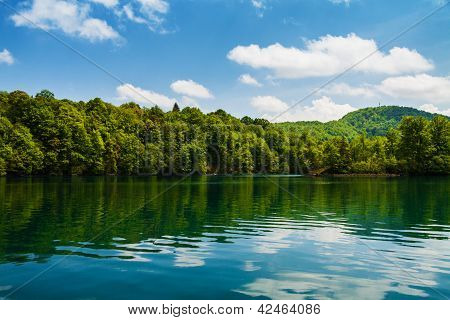Forest And Clouds With Reflection In A Calm Lake