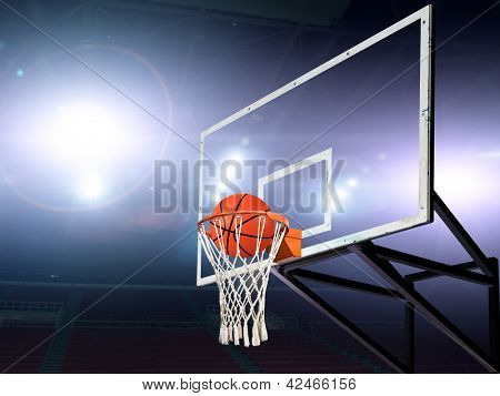Basket ball inside the net with spotlights