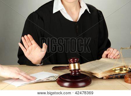 Juiz sentado à mesa durante audiência sobre fundo cinza