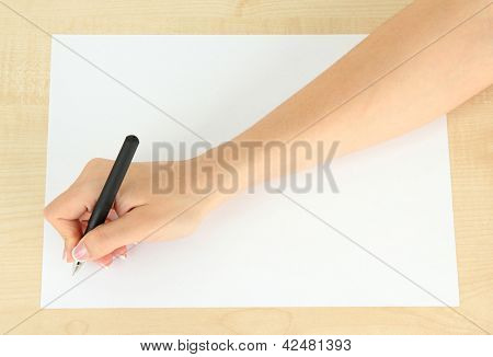 Hand with pen on white paper, on wooden background