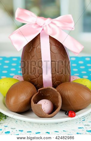 Composition of Easter and chocolate eggs on window background