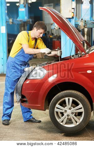 One young auto mechanic tighten screw with spanner during automobile car maintenance at engine auto repair shop service station