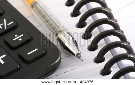 Ballpen And Calculator On Notebook