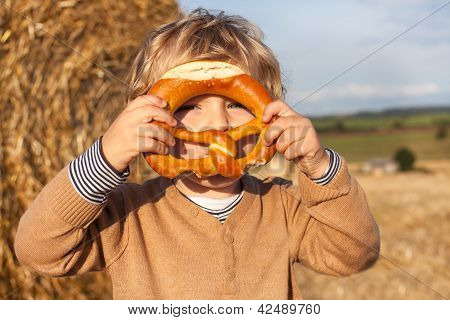 Cute Toddler Eating German Pretzel On Goden Hay Field