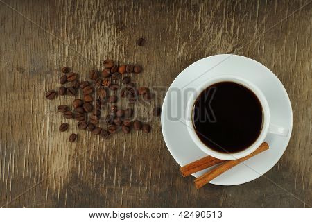Cup of coffee with beans and cinnamon sticks