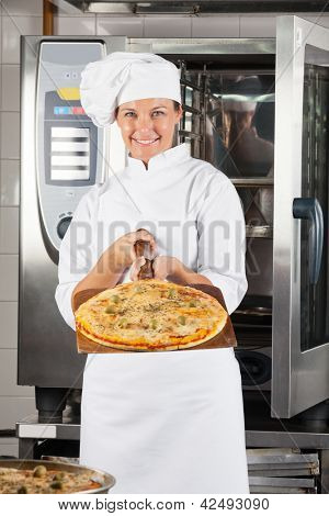 Portrait of confident female chef presenting pizza at commercial kitchen