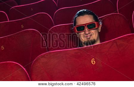 Funny young man in 3D glasses watching movie in cinema