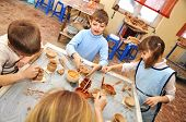 .group Of Children Shaping Clay In Pottery Studio