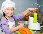 girl  making fresh carrot juice with a juice extractor