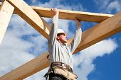 stock photo of handyman  - carpenter at work with wooden  roof construction - JPG