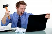 stock photo of frustrated  - A businessman about to smash his laptop with a hammer - JPG