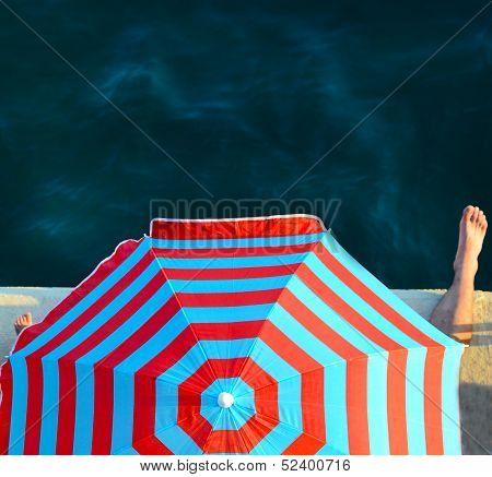 Funny image of father and son sitting under sunshade on the seashore