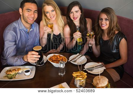 High angle view of happy friends having dinner together looking at camera