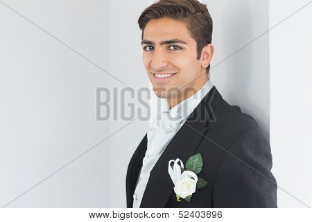 Cute bridegroom leaning against a wall smiling at camera