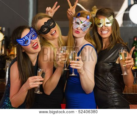 Attractive women wearing masks holding champagne looking at camera