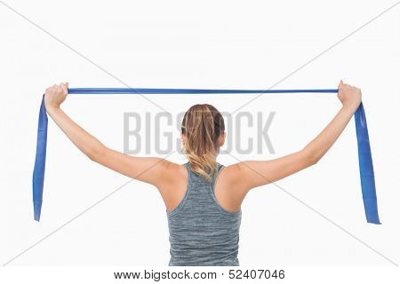Pony tailed woman training with a resistance band on white background