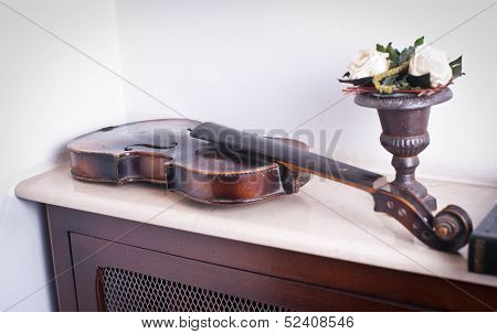 old violin near a vase with roses