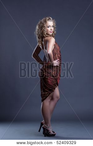 Coquettishly smiling curly girl posing in negligee