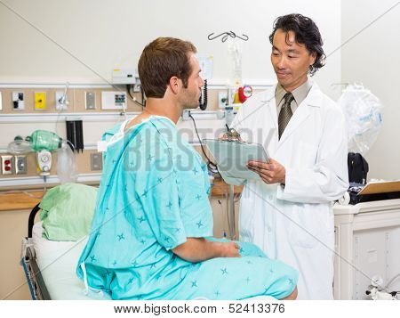 Male doctor examining patient's report in hospital room