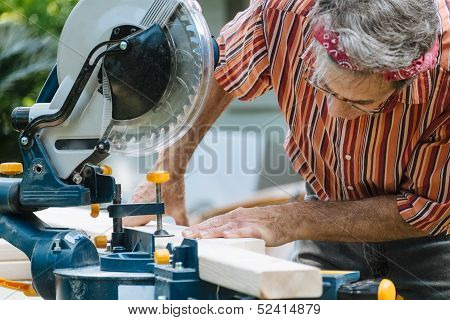 Man Sawing Wood With Sliding Compound Miter Saw Closeup