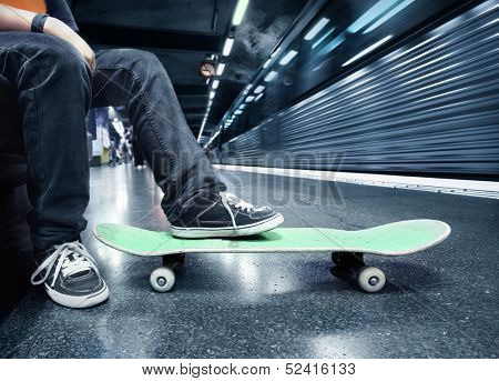 Boy at the subway station with his skateboard