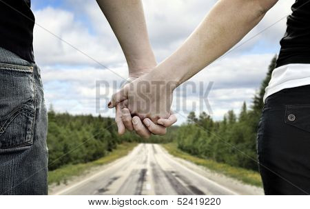 A couple holds hands on a country road